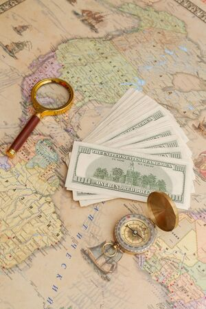 A bundle of American dollars lies with a compass and a magnifying glass on the world map