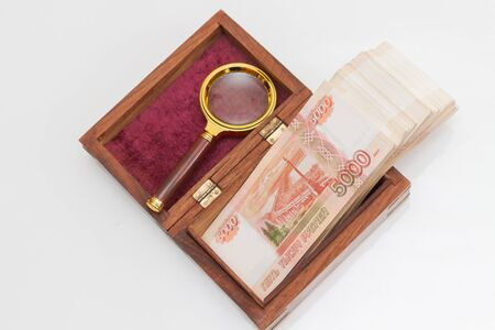 Russian banknotes of five thousand rubles in large quantities in a wooden box with a magnifying glass