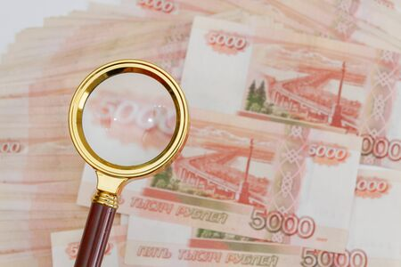 A magnifying glass with a gold handle is placed on top of Russian banknotes of five thousand rubles in large quantities