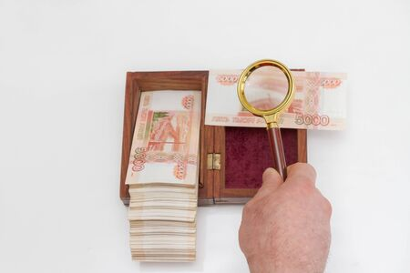 A man's hand holds a magnifying glass over a wooden box with a large stack of Russian five thousand rubles bills