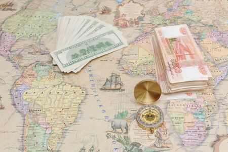Compass with a bundle of big money are on the map