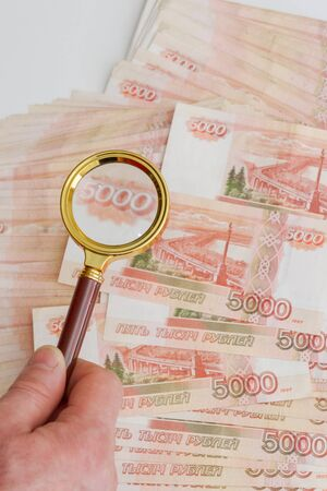 A man's hand holds a magnifying glass with a gold handle over a large number of Russian banknotes worth five thousand rubles