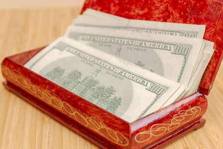 American hundred dollar bills in large quantities in a wooden box