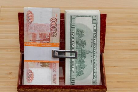 American hundred dollar bills and a large wad of Russian five thousand bills in a wooden box