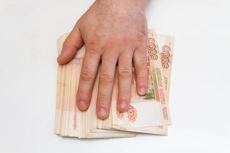 A man's hand counts and shifts a large number of five thousand rubles bills into a stack