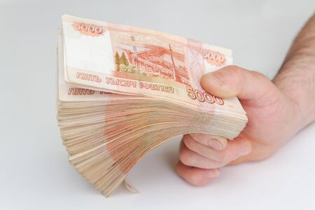 Men's hands hold a large number of banknotes in a pack of five thousand rubles Banque d'images