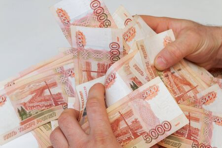 Men's hands hold a large amount of money with Russian banknotes of five thousand rubles