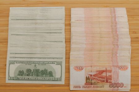 A large number of American hundred dollar bills and Russian five thousand dollar bills Фото со стока
