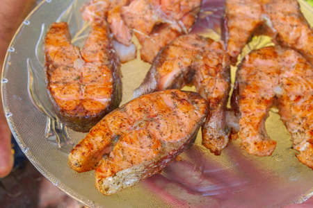 Grilled red fish trout steaks lie on a glass plate