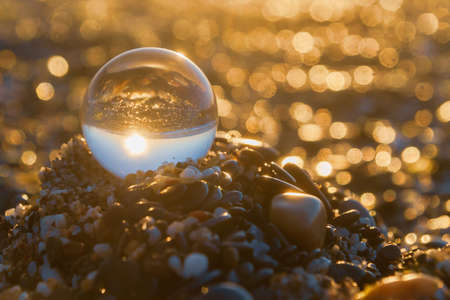 Glass round ball on the beach reflects the sea in summer at sunset Banco de Imagens
