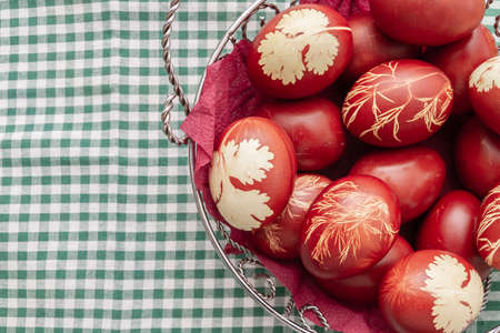 Painted Easter eggs in onion husks with abstract drawings are in a basket