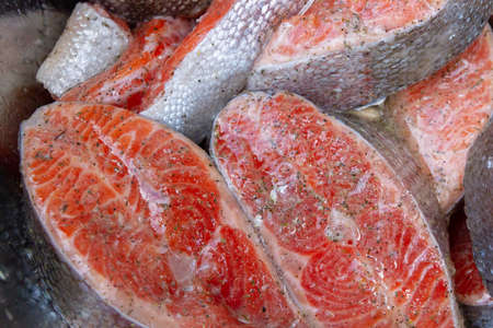 Fresh trout steaks are marinated in a metal bowl before cooking