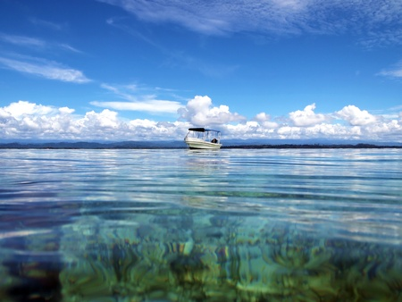 archipelago: Isolated boat with calm water surface and cloudy sky, Bocas del Toro