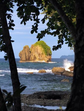Small island with waves crashing on the coast. Caribbean coast. photo