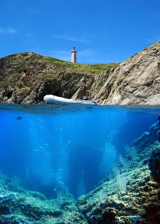 port vendres: Surface and underwater view with cliff, lighthouse and bubbles divers Stock Photo