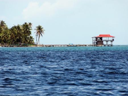 Tropical stilt restaurant over the Caribbean sea with coconuts trees, Bocas del Toro, Panama photo
