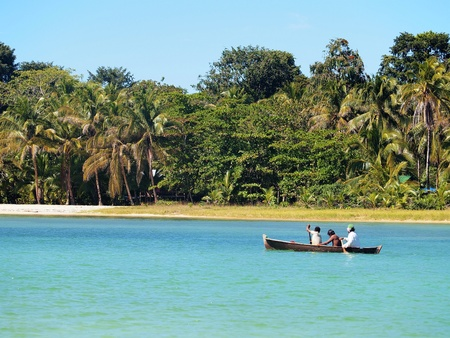 dugout: Dugout canoe with amerindian people near a beach in Bocas del Toro, caribbean sea, Panama