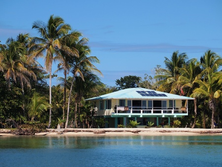 stilt house: Beach house with solar panels and tropical vegetation Editorial