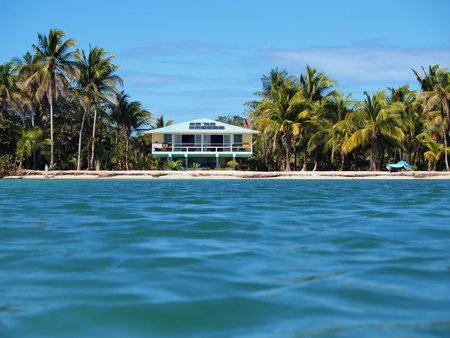 bahamas: Tropische kust met zonne-energie huis aan het strand en palmbomen