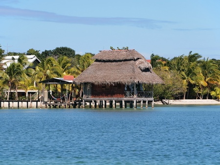 Stilt cabin with thatched roof and white sand beach in background photo