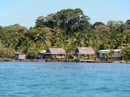 Small Amerindian village on a beach with thatched hut and coconut trees, Caribbean, Panama photo