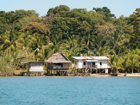 thatched house: Typical Caribbean houses on a beach with tropical vegetation, Panama Stock Photo