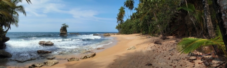 Panorama over a pristine beach with some rocks and lush vegetation, Caribbean