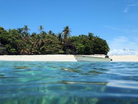 bahamas: Uitzicht vanaf het water oppervlak van een wit zandstrand met een boot en tropische vegetatie Stockfoto