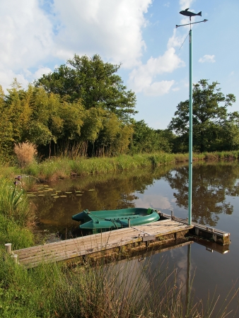 Floating dock on a pond with a small boat and a weather vane photo
