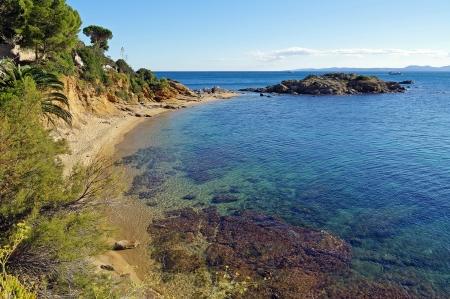 Belle plage de la Méditerranée aux eaux claires et une petite île rocheuse, Costa Brava, Catalogne, Espagne