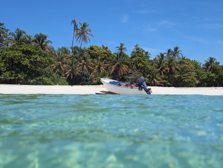 Boat on a white sandy beach with turquoise water and beautiful tropical vegetation photo