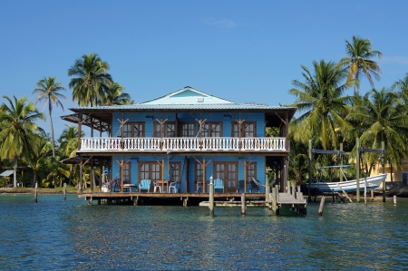 Beautiful Caribbean stilt house over the sea with coconut trees in background