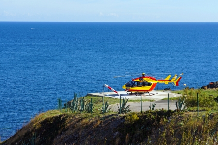 ec: Helicopter EC-145 on a landing area with Mediterranean sea in background,Vermilion Coast, Roussillon, France
