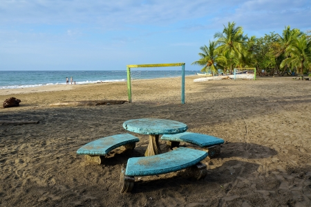 Tropical beach with a round table and benches in foreground, football pitch with goals on the sand, Caribbean, Manzanillo, Costa Rica photo