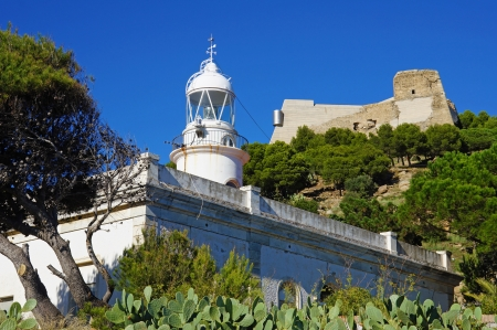 queen isabella: The Rosas lighthouse, built in 1864 under Queen Isabella II, below the Trinity Castle, Costa Brava, Mediterranean sea, Spain Editorial
