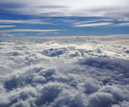 altitude: View from the hublot of an airplane flying in a cloudy sky