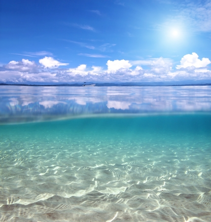 Underwater and surface view with clouds reflected on water surface and ripples of sunlight on a sandy sea floor