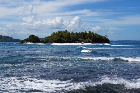 swell: Beautiful unspoiled island with lush vegetation and rough sea, Bocas del Toro archipelago, Bastimentos, Caribbean sea,  Stock Photo