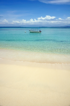 Tropical sandy beach with clear water and a boat alone in the Caribbean sea photo
