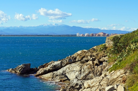 costa brava: Rocky coast of the Mediterranean sea with Pyrenees mountains and buildings in background, gulf of Roses in Costa Brava, Catalonia, Spain Stock Photo