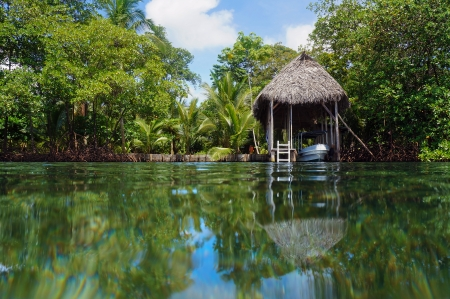 boathouse: Boathouse with palm roof and lush tropical vegetation reflected on water surface, Bocas del Toro, Caribbean sea, Central America, Panama