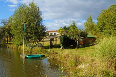 Cabin at the edge of a pond with a small boat and the main house in background photo
