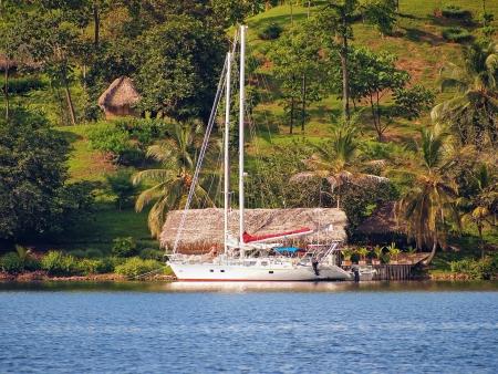 palapa: Coast with a sailboat, coconuts trees and a cabin in Bocas del Toro, caribbean sea, Panama