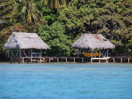 boathouse: Boathouse and palapa over the sea with luxuriant tropical vegetation Stock Photo