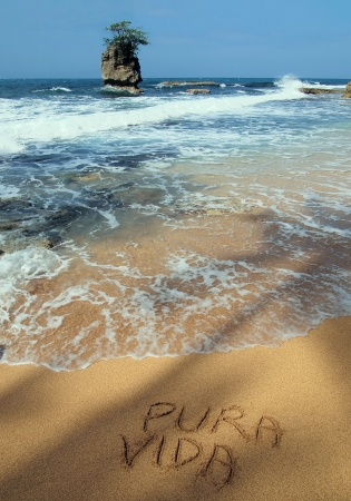 The words pura vida written in the sand on a beach, Costa Rica