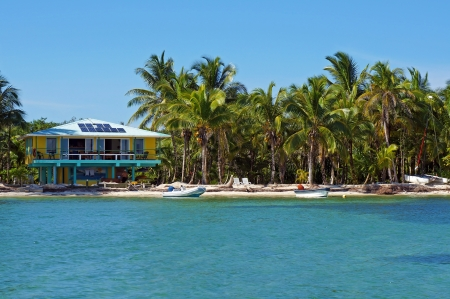 Tropical seashore with solar powered beach house and coconut trees, Caribbean, Bocas del Toro, Panama