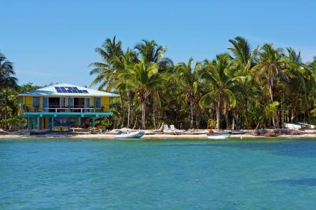 Tropische kust met zonne-energie beach house en kokospalmen, het Caribisch gebied, Bocas del Toro, Panama Stockfoto