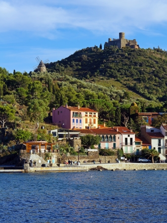 vermilion coast: Seashore in the village of Collioure with windmill and castle in background, Mediterranean sea, Roussillon,Vermilion coast, France