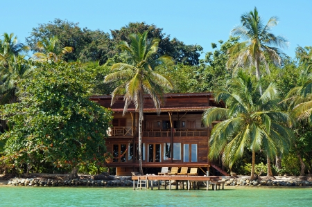 panama: Tropical waterfront beach house with lush vegetation, Caribbean, Bocas del Toro, Panama Stock Photo