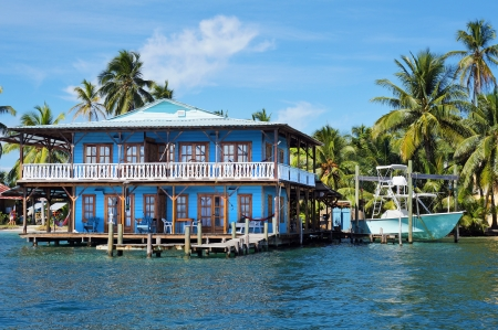 Beautiful tropical house on stilts over the Caribbean sea with a boat and coconut trees, Panama